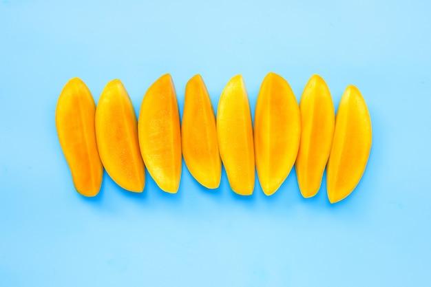 Fruits tropicaux, tranches de mangue sur fond bleu.