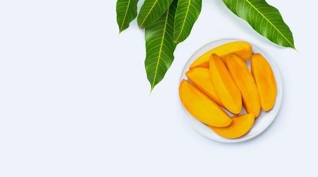 Fruits tropicaux, tranches de mangue sur plaque sur blanc isolé. vue de dessus