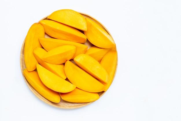 Fruits tropicaux, tranches de mangue sur une plaque en bois sur fond blanc.