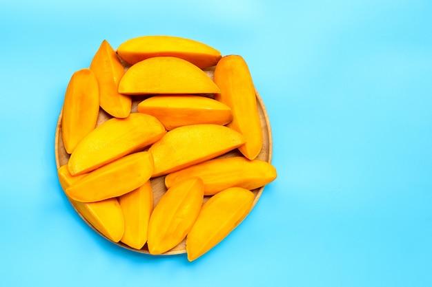 Fruits tropicaux, tranches de mangue sur plaque en bois sur fond bleu. vue de dessus