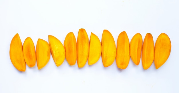 Fruits tropicaux, tranches de mangue sur une surface blanche. vue de dessus