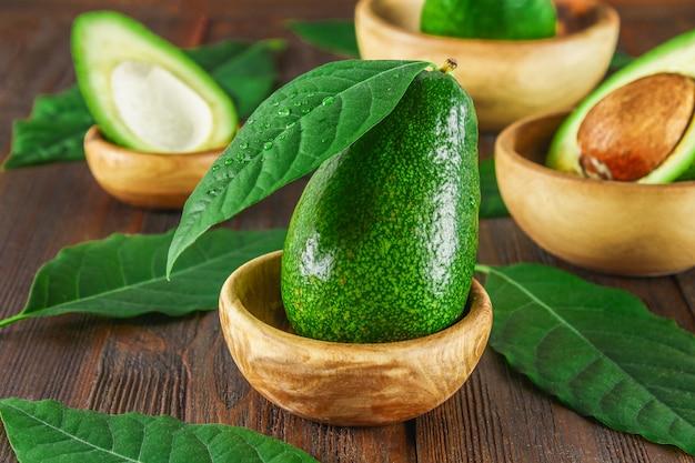 Des fruits verts et entiers, coupés mûrs et entiers avec pierre se trouvent dans des bols en bois