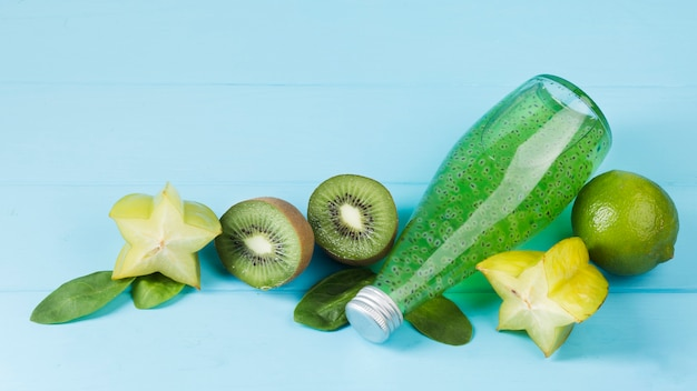 Fruits verts frais et bouteille sur fond bleu