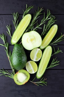 Fruits verts, légumes et romarin sur des tableaux noirs avec copie espace. avocat, citron vert, kiwi et pomme verte sur des planches en bois. vue de dessus des concombres et des branches de romarin. nourriture saine