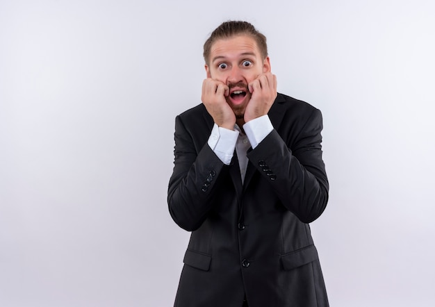 Frustré bel homme d'affaires portant costume choqué regardant la caméra debout sur fond blanc