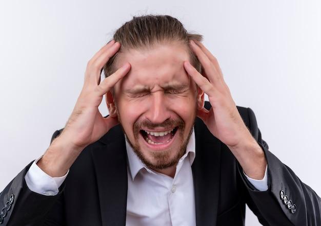 Frustré bel homme d'affaires portant costume tenant sa tête avec les mains debout sur fond blanc