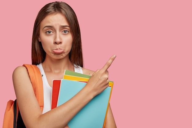 Frustré étudiant offensé posant contre le mur rose
