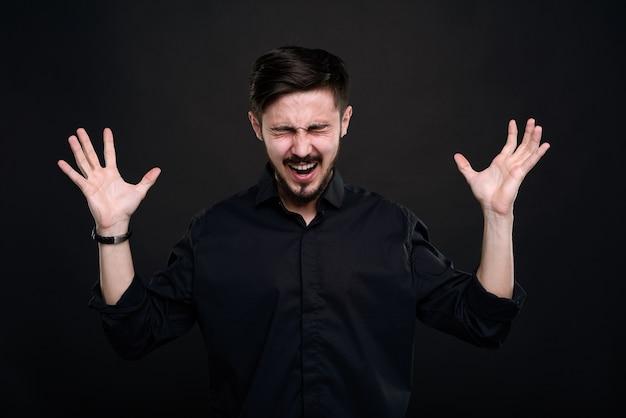 Frustré jeune homme barbu agacé par l'échec hurlant les yeux fermés et se serrant la main de colère