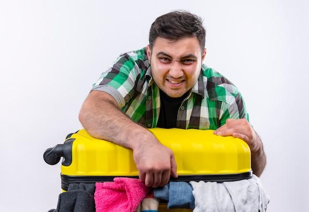 Frustré jeune homme voyageur en chemise à carreaux debout avec valise pleine de vêtements tryinbg pour le fermer avec un visage en colère sur un mur blanc