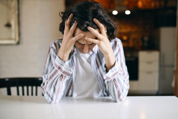 Frustré, malheureux jeune homme ayant un regard déprimé, regardant vers le bas, tenant les mains sur sa tête, stressé par des problèmes financiers parce qu'il s'est fait virer.