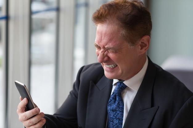 Frustré senior manager holding mobile phone