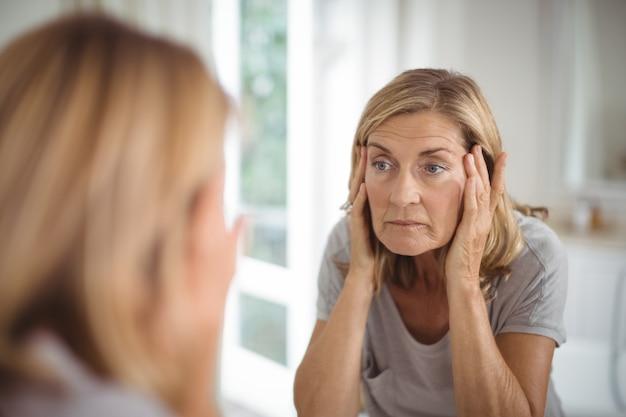 Frustré senior woman looking at mirror