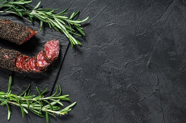 Fuet, salami et un brin de romarin. saucisse espagnole traditionnelle. fond noir. vue de dessus. espace pour le texte