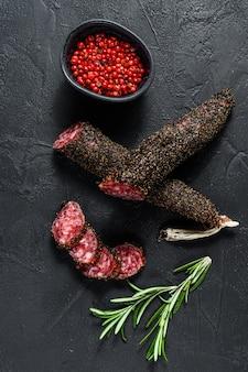 Fuet, salami et un brin de romarin. saucisse espagnole traditionnelle. fond noir. vue de dessus