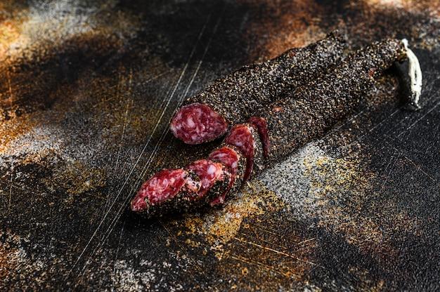 Fuet, salami. saucisse espagnole traditionnelle. fond noir. vue de dessus