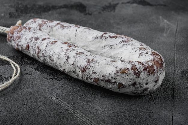 Fuet de saucisse de salami sec sur une table texturée grise.