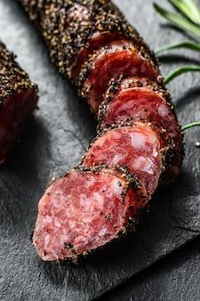Fuet de saucisse. saucisse de porc. antipasto italien. mur noir. vue de dessus