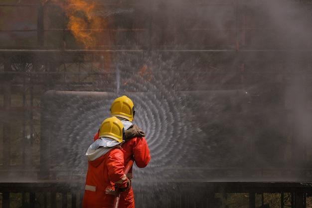 Fuite de gaz du tuyau et soupape de flamme de la fuite de gaz. lutte contre l'incendie avec des extincteurs et un tuyau d'incendie.