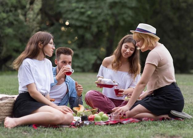 Full shot amis boire du jus à l'extérieur
