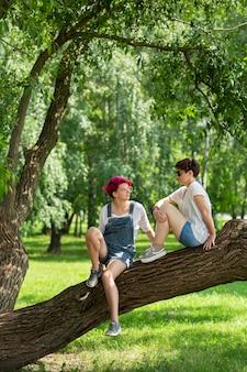 Full shot amis sur tronc d'arbre
