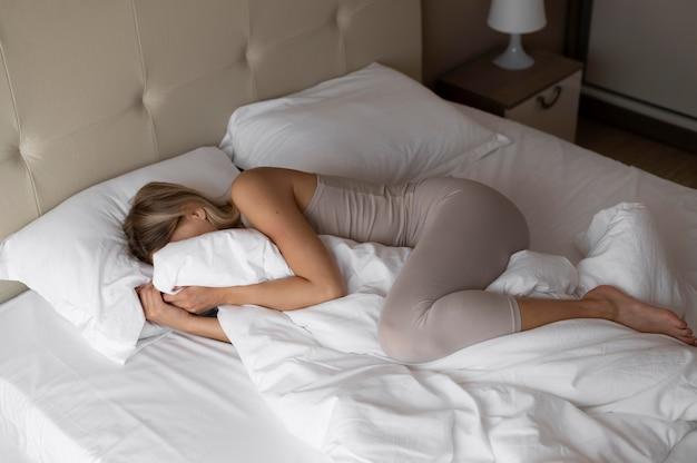 Full shot femme allongée dans son lit