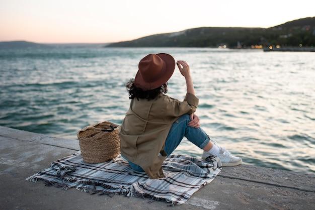 Full shot femme assise sur une couverture