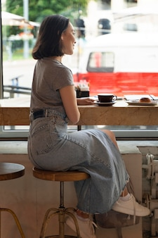 Full shot femme assise avec du café