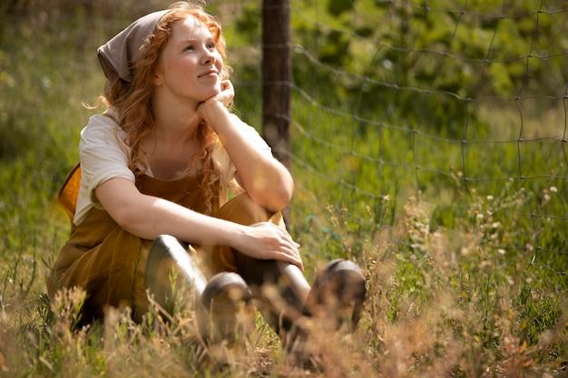Full shot femme assise sur l'herbe