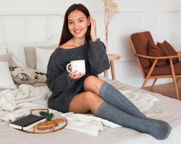 Full shot femme assise sur le lit avec du lait, des biscuits et de l'ordre du jour