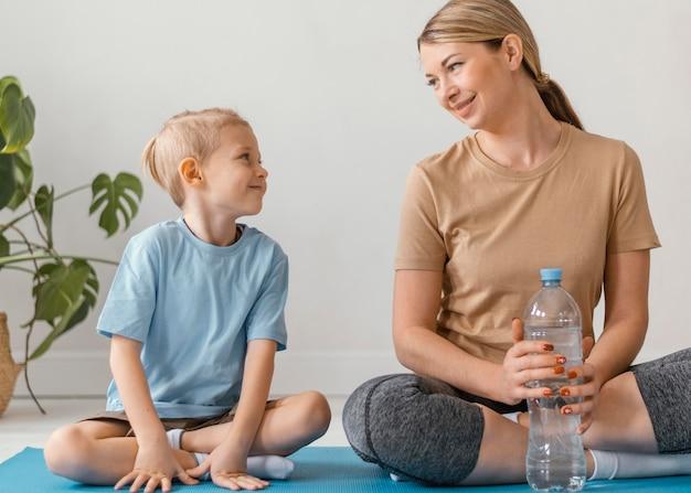 Full shot femme et enfant assis sur un tapis
