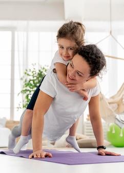 Full shot femme faisant planche avec enfant