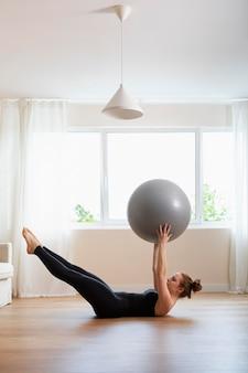 Full shot femme formation avec ballon de gym