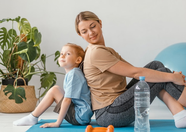 Full shot femme et garçon assis sur un tapis