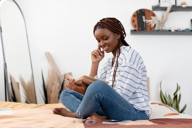 Full shot femme lisant à la maison
