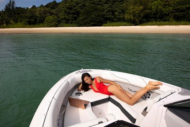 Full shot femme avec ordinateur portable sur bateau