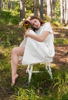Full shot femme posant avec des fleurs