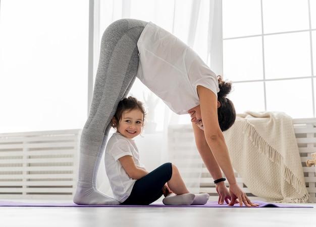 Full shot femme qui s'étend avec enfant