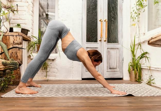 Full shot femme sur un tapis de yoga qui s'étend