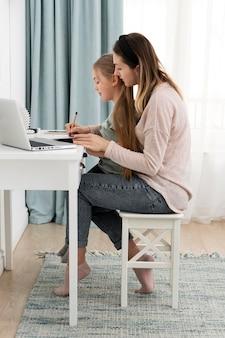 Full shot femme travaillant à la maison avec enfant