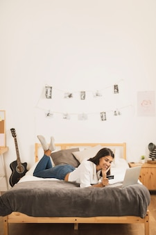 Full-shot, femme, travailler, ordinateur portable, dans lit