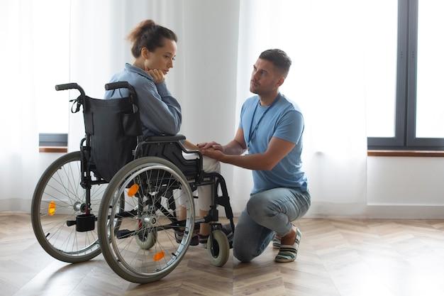 Full shot femme triste en fauteuil roulant