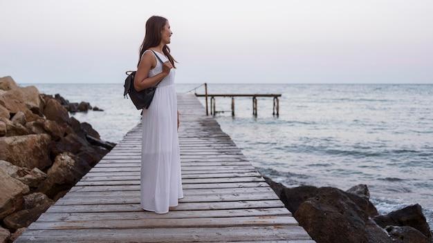 Full shot femme vêtue d'une robe blanche