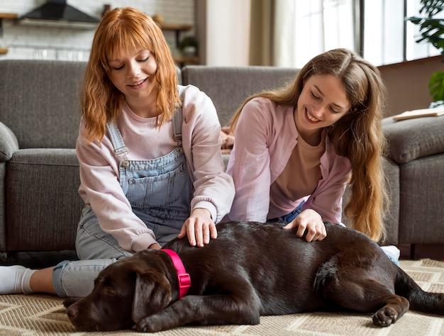 Full shot femmes caresser le chien