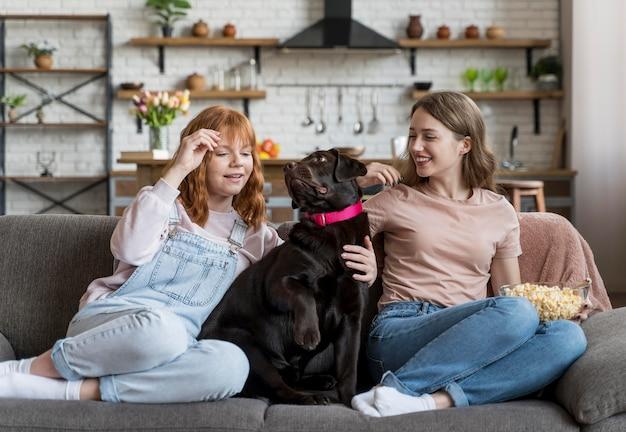 Full shot femmes et chien assis ensemble