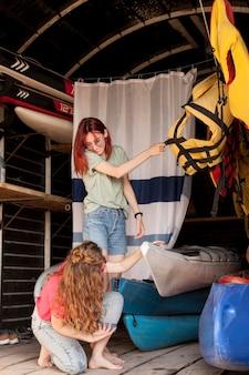 Full shot femmes prenant kayak de hangar