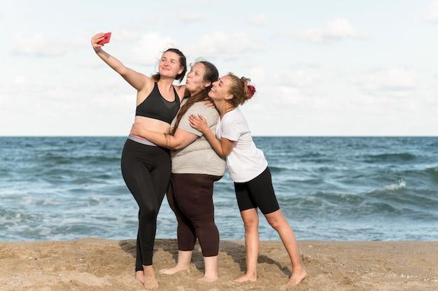 Full shot femmes prenant des selfies ensemble