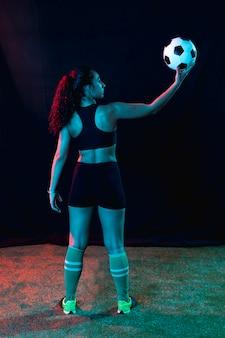 Full shot fit jeune fille avec ballon de foot