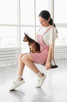 Full shot girl sur balançoire avec chien
