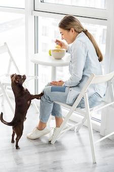 Full shot girl manger le petit déjeuner avec un chien