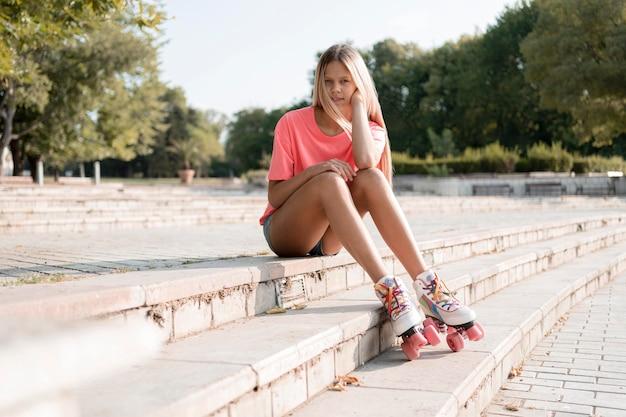 Full shot girl portant des patins à roulettes